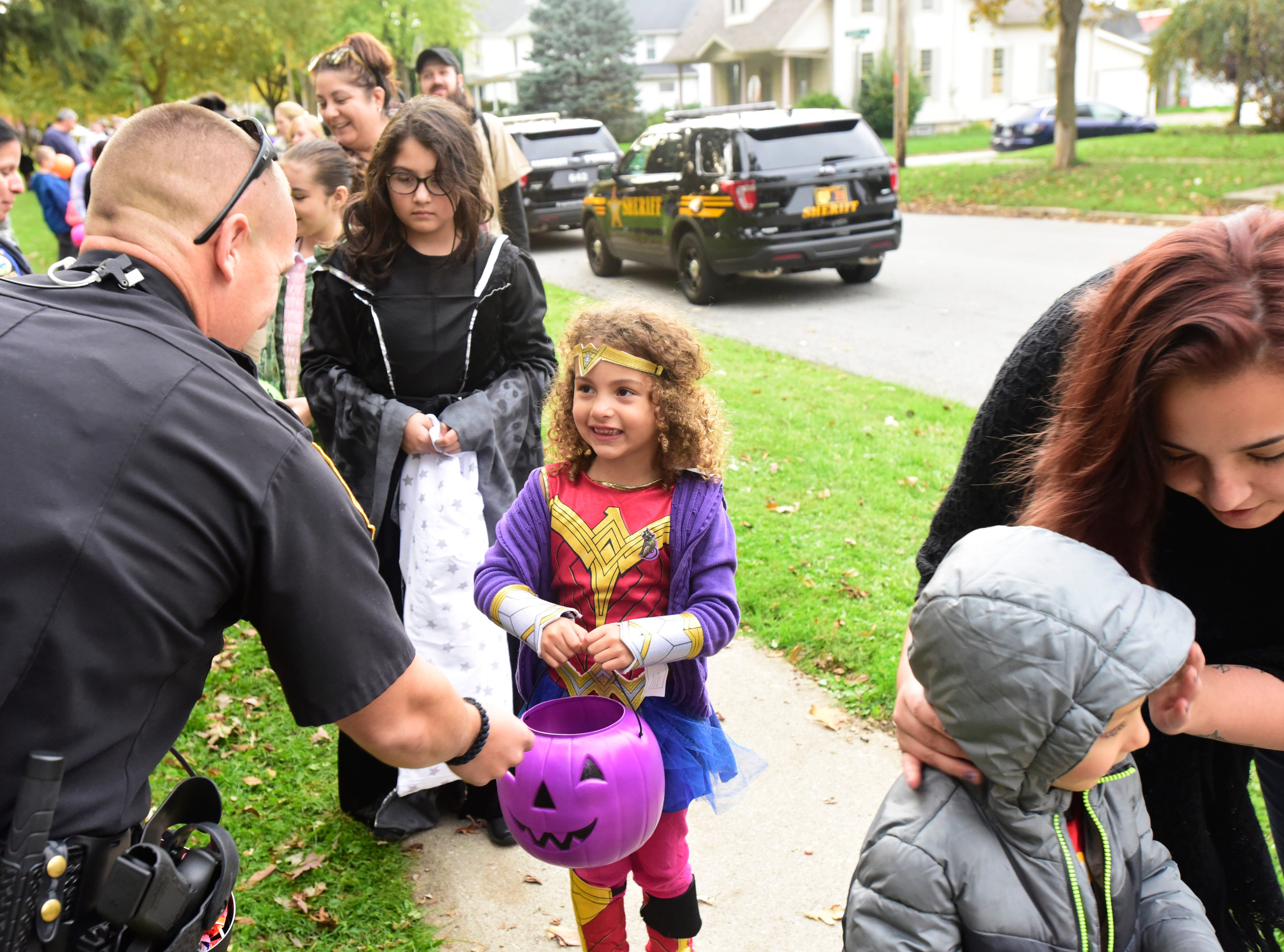 Deputy Gary Pollock of the Sandusky County Sheriff's Office gives candy to Ana'Leigh Sims, 5, of Fremont during Candy with the Cops at Birchard Park on Tuesday evening.
