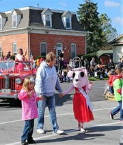 Marie Darr walks with Fiona Chell and Elizabeth Murphy dressed as Princess Fiona during the Oak Harbor Apple Festival Parade.