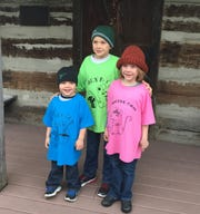"""From left, Henry, Patrick and Fiona Chell stand  in front of the Log Cabin in Adolphus Kraemer Park in Oak Harbor.  This cabin is home to the mouse family in """"Fiona's Bucket of Trouble"""" by Nan Rebik and Carole Hinkleman."""