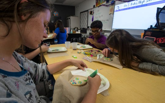 Kelsea Gard, 17, an 11th grader at Ida Baker High School, decorates a cookie for halloween as part of an exercise in her life skills class for exceptional students Monday, October 29, 2018. It was part of a special ceremony where Best Buddies were paired up.