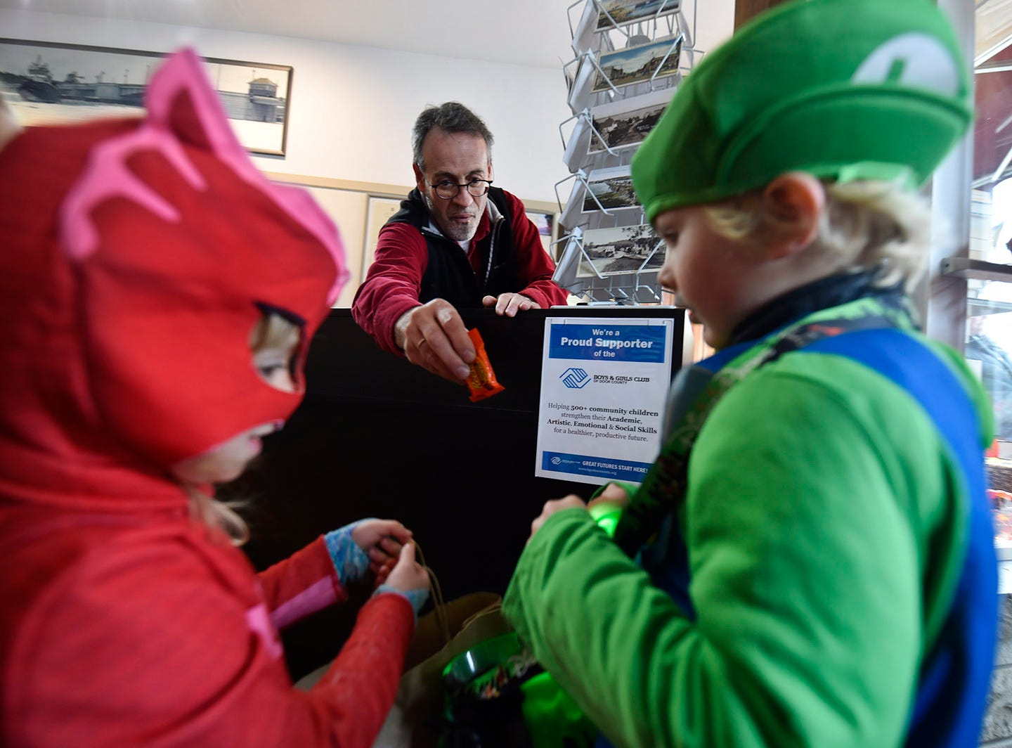 John Maggitti hands out more candy inside Bay Novel Booksellers following the Thrills on Third costume parade on Saturday, Oct. 27, 2018, in Sturgeon Bay. Tina M. Gohr/USA TODAY NETWORK-Wisconsin