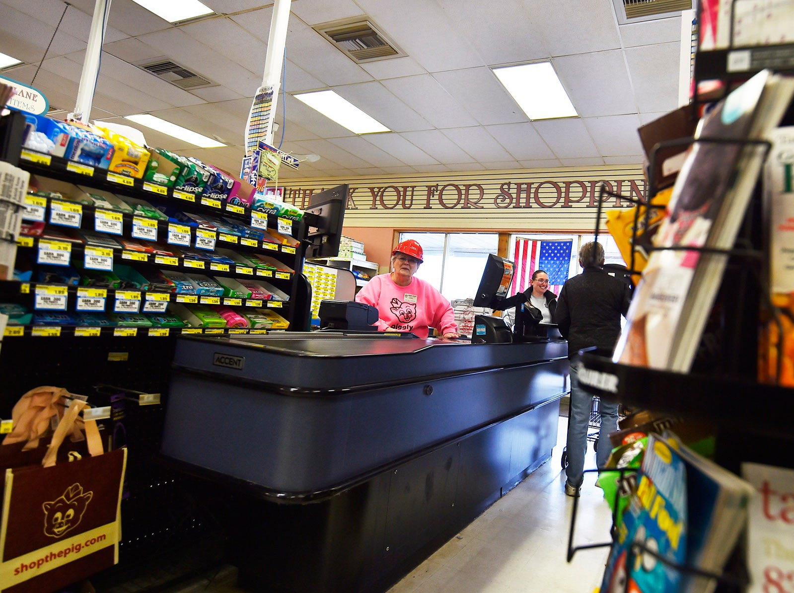 Joining the expansion atmosphere by wearing a hard hat, Lois Lindstrand greets customers at the check-out at Piggly Wiggly Sister Bay on Oct. 29, 2018. Tina M. Gohr/USA TODAY NETWORK-Wisconsin