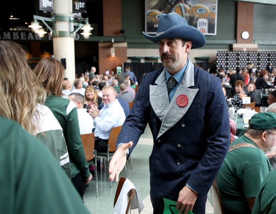 Green Bay Packers quarterback Aaron Rodgers greets people at his table during the Green Bay Chamber of Commerce Welcome Back Packers Luncheon at Lambeau Field in August.