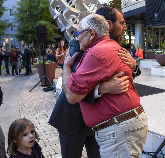 Ted Hammer, right, hugs Rabbi Leibil Kesselman of Greenville before a vigil for the victims from the Tree of Life Synagogue in Pittsburgh, a moment of reflection in the NOMA Square in downtown Greenville on Tuesday.