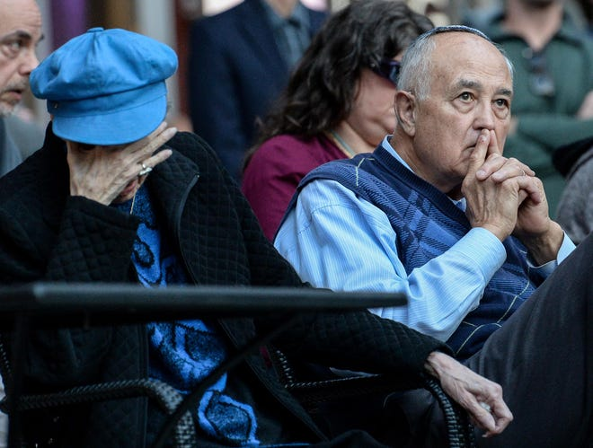 Faith St. Claire, left, and her husband Robert St. Claire of Greenville, both with the Congregation Beth Israel, listen to a speech by Rabbi Mathew Marko during a vigil for the victims from the Tree of Life Synagogue in Pittsburgh, a moment of reflection in the NOMA Square in downtown Greenville on Tuesday.