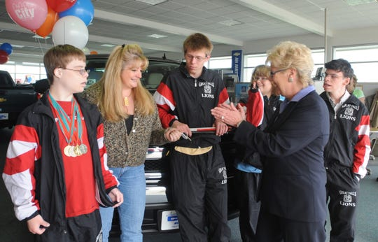 Leslie Oakland, of City Motors, applauds after presenting the keys to a new pickup to Nancy Steffens , who won the truck in the Montana Special Olympics raffle in 2008.  Alson applauding are Special Olympians Jared Radeen, Ricky Puzon, Mary Peters and Matt Lyons.