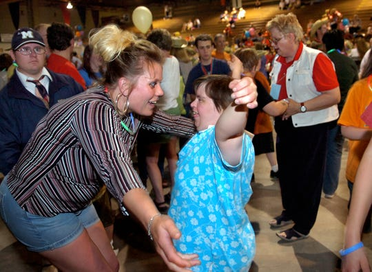 Special Olympics athlete Karla Garsjo of Glasco get a hug from her coach Kristy Zemlinsk while they dance during a dance and carnival in the Four Seasons Arean in Great Falls during the Montana State Special Olympics on Thursday, May 17, 2007.