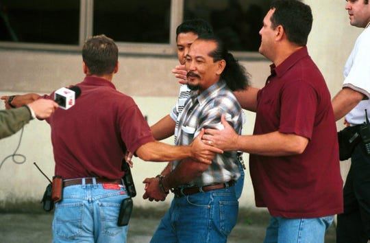 In this January 2000 file photo, former Sen. Angel Santos is taken away by U.S. Marshals after being sentenced to six months for contempt in  the U.S. District Court of Guam.  A judge found Santos in contempt after Santos cleared federal land he said belongs to his family.