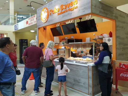 A small crowd gathers in front of Poke Seven Seafood & Veggies at the Agana Shopping Center.