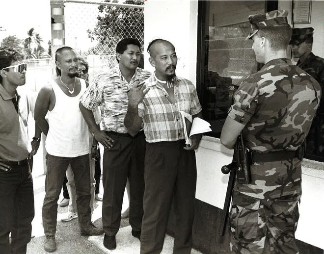 In the 1992 file photo, Angel Santos of the Chamoru Nation Traditional Council presents a statement of warning to sentry guard Scott Stormer at Naval Air Station in Barrigada. Santos, an activist, went on to become a senator.