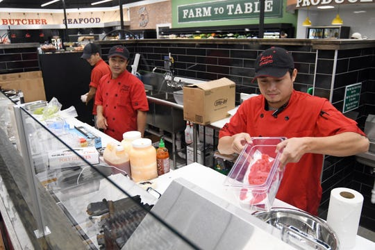 Workers prepare sushi as the Corner Market at Midtown opens their store to the public on Wednesday, October 31, 2018.