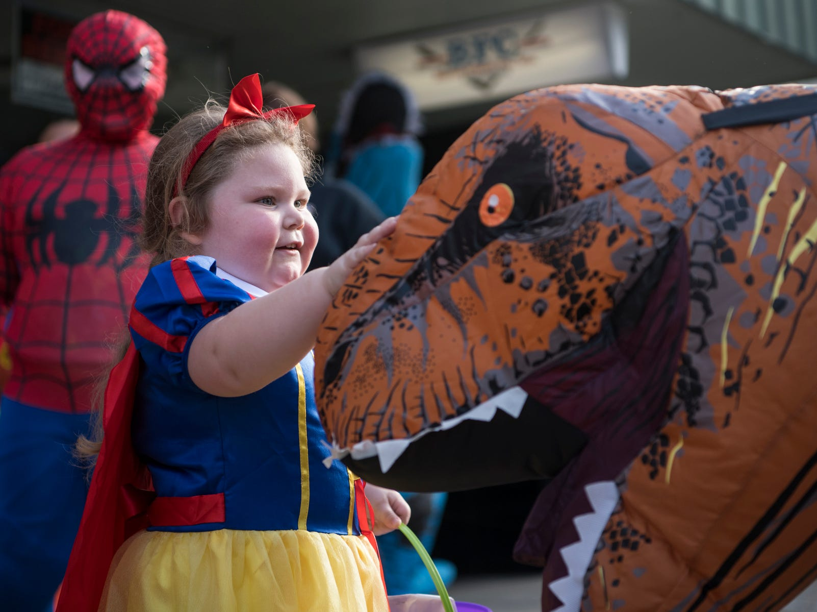 Avery Brummitt, 3, pets Whitney Floyd's inflatable dinosaur costume outside of Field and Main Insurance on North Main Street during the trick-or-treat event in downtown Henderson, Ky., Tuesday, Oct. 30, 2018. Field and Main Insurance employees displayed a Jurassic Park theme as they passed out candy to the children walking by.