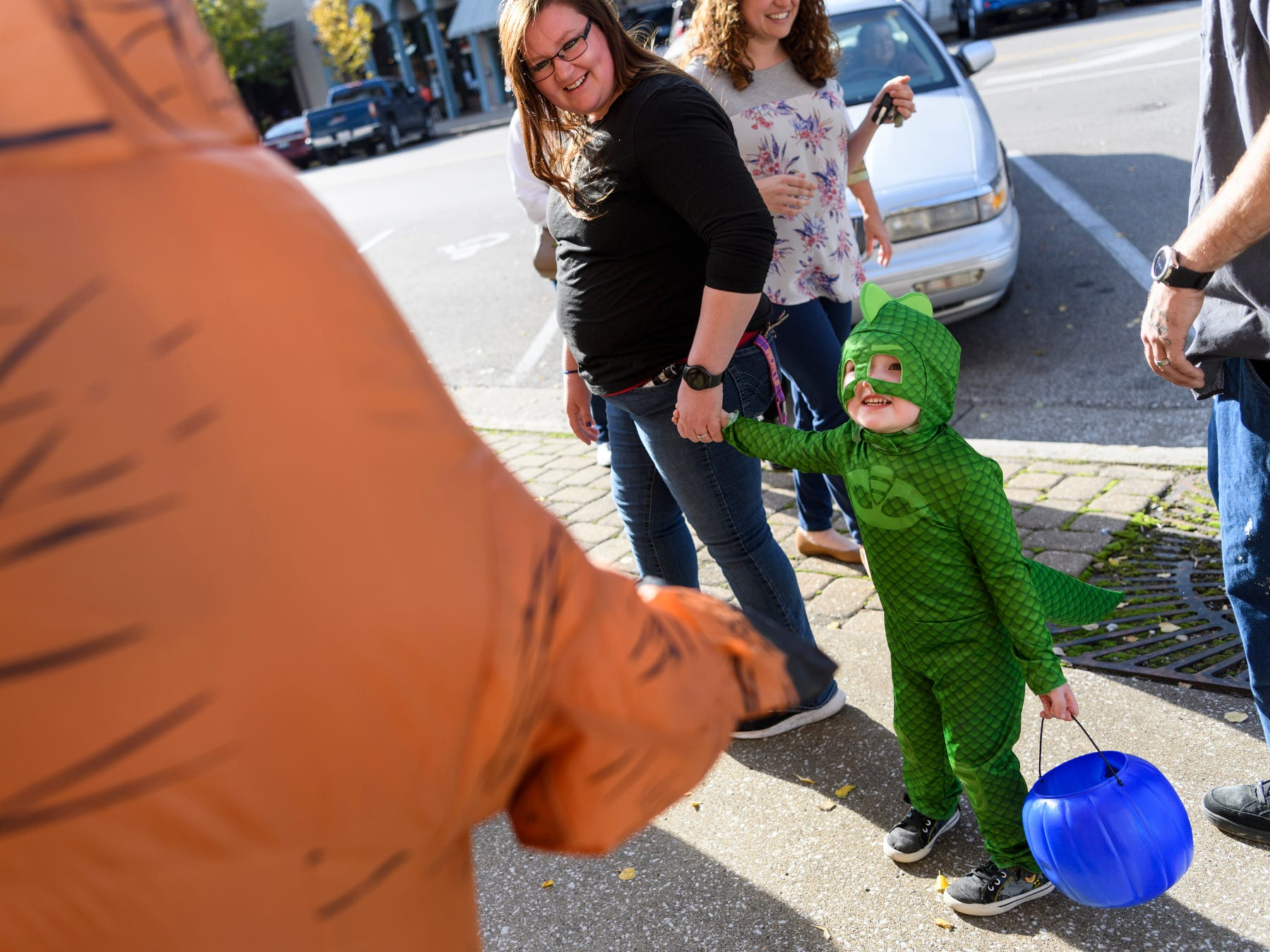 Three-year-old AJ Biggers, right to left, and his mother Samantha Biggers are greeted by Bill Latta of Field and Main Insurance, who is decked out in an inflatable dinosaur suit, along N. Main Street in downtown Henderson, Ky., Tuesday, Oct. 30, 2018. Due to a forecast calling for significant rain on Halloween Day, the Rotaract of Henderson moved it's Downtown Trick-Or-Treat event to Tuesday evening from 3-5 p.m.
