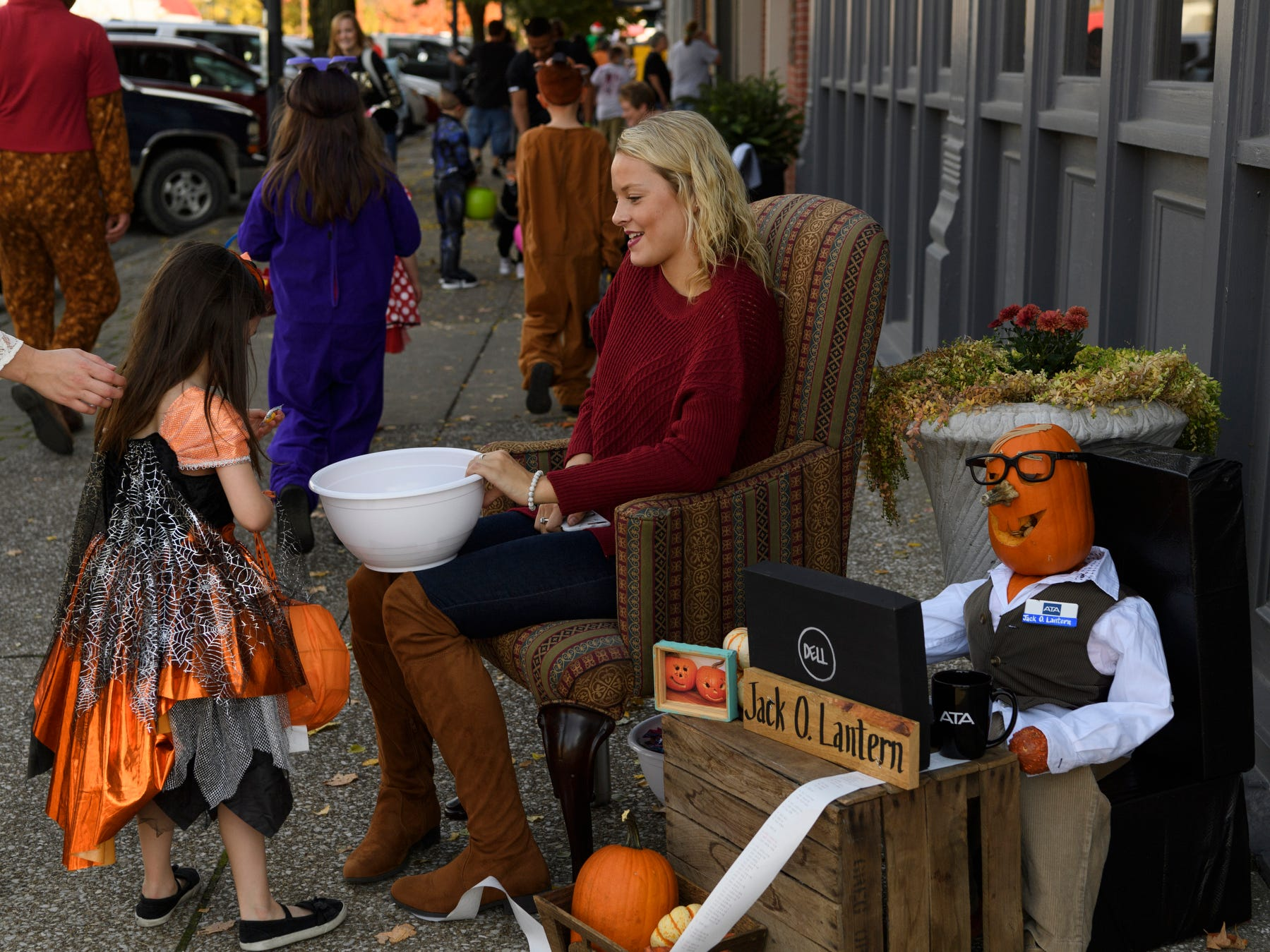 Carlee Carfton of ATA Certified Public Accountants hands out candy to trick-or-treaters along First Street in downtown Henderson, Ky., Tuesday, Oct. 30, 2018.
