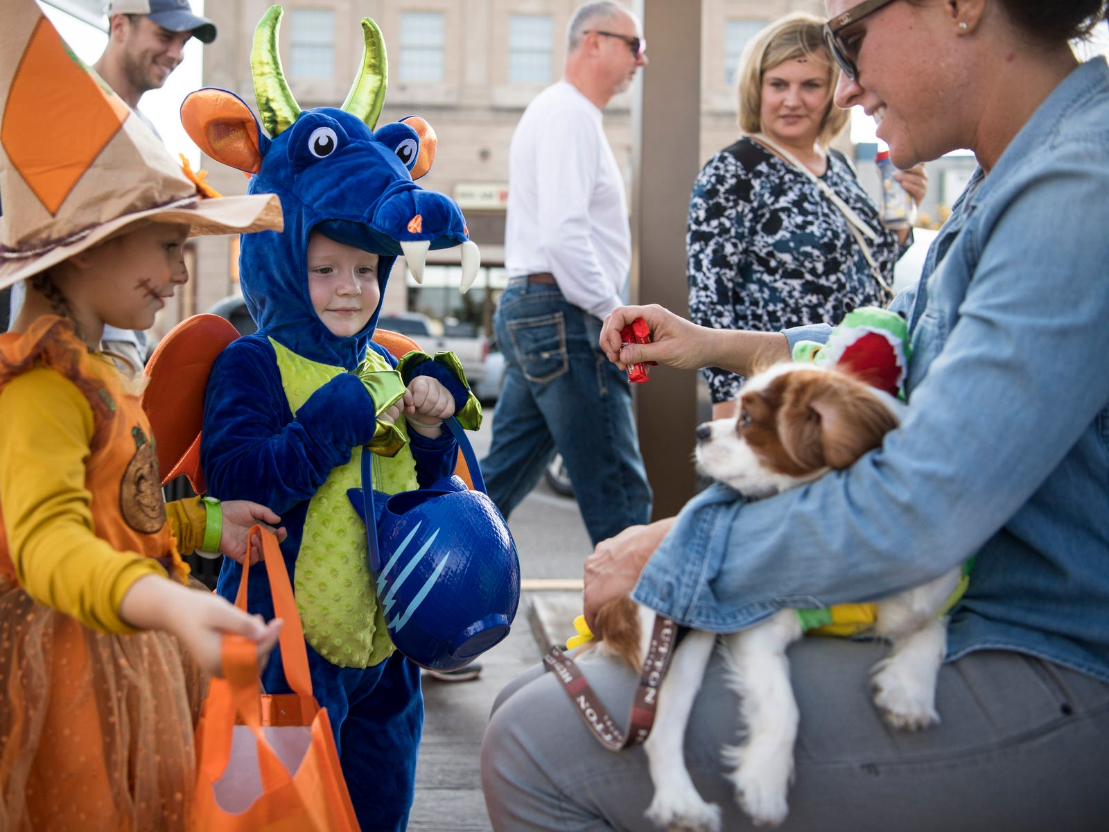 Lindsay Locasto of the Downtown Henderson Partnership, from right, and her dog Charley hand out candy to Rhett Abbot, 2, and Harlow Burke, 4, during the Trick-or-Treat event at the Central Business District in downtown Henderson, Ky., Tuesday, Oct. 30, 2018.