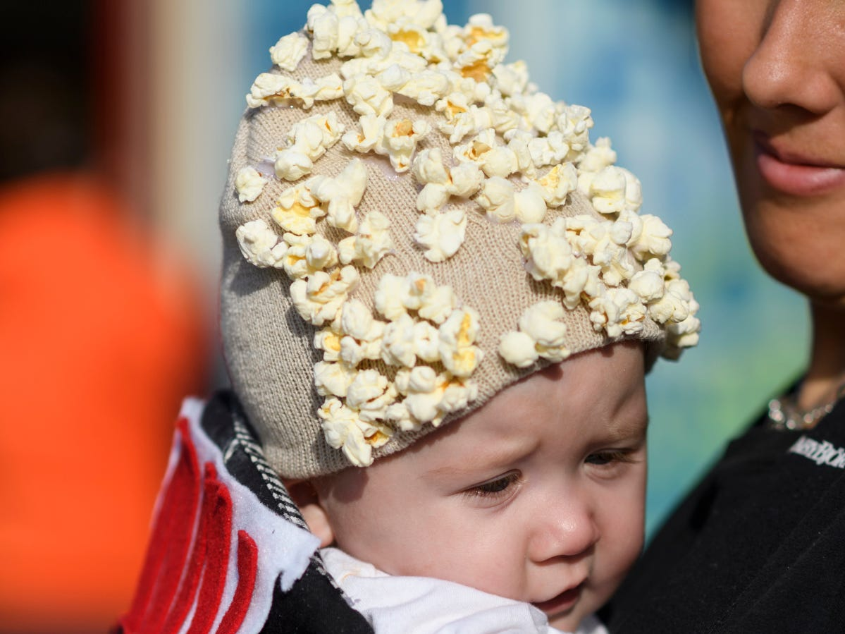 Six-month-old Oakley Overfield is dressed as a tub of popcorn during the trick-or-treat event along the Central Business District in downtown Henderson, Ky., Tuesday, Oct. 30, 2018. He was carried around the streets by his mother Halley Overfield.