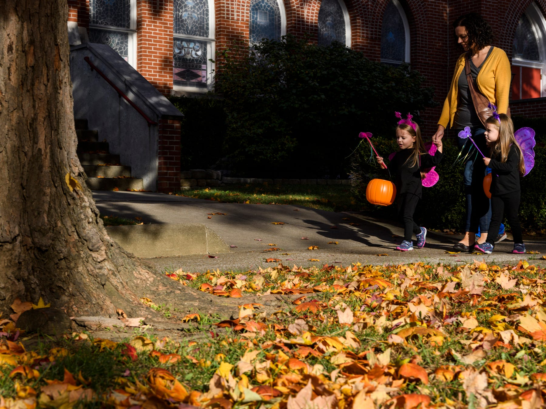 Twin sisters Emily Clutts, left, and Nora Clutts, right, walk to the next candy stop with their mother Mary Clutts, during the Trick-or-Treat event in downtown Henderson, Ky., Tuesday, Oct. 30, 2018.