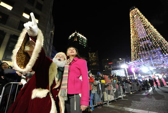 Santa Claus and Kimberly Montes de Oca, the coloring contest winner who turned on the Christmas lights, walk through the crowd during the Circle of Lights presented by Quality Connection and IBEW 481 on Monument Circle Friday, November 29, 2013.