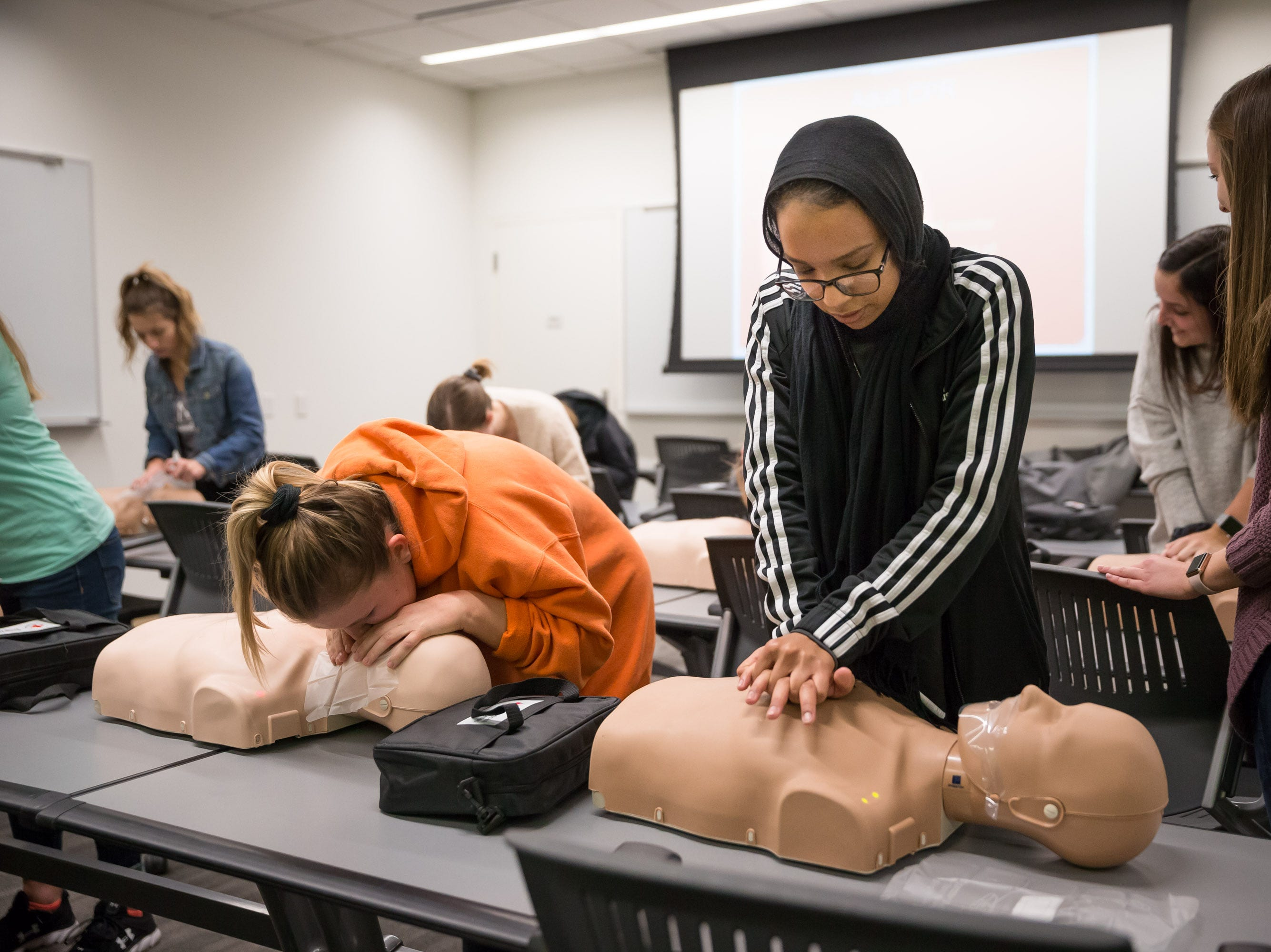 University of Iowa studetns Emma Kirincich, left, and Ebteehal Ismail practice CPR breaths and compressions on test dummies at the UI Campus Recreation & Wellness Center on Monday, October 29, 2018.