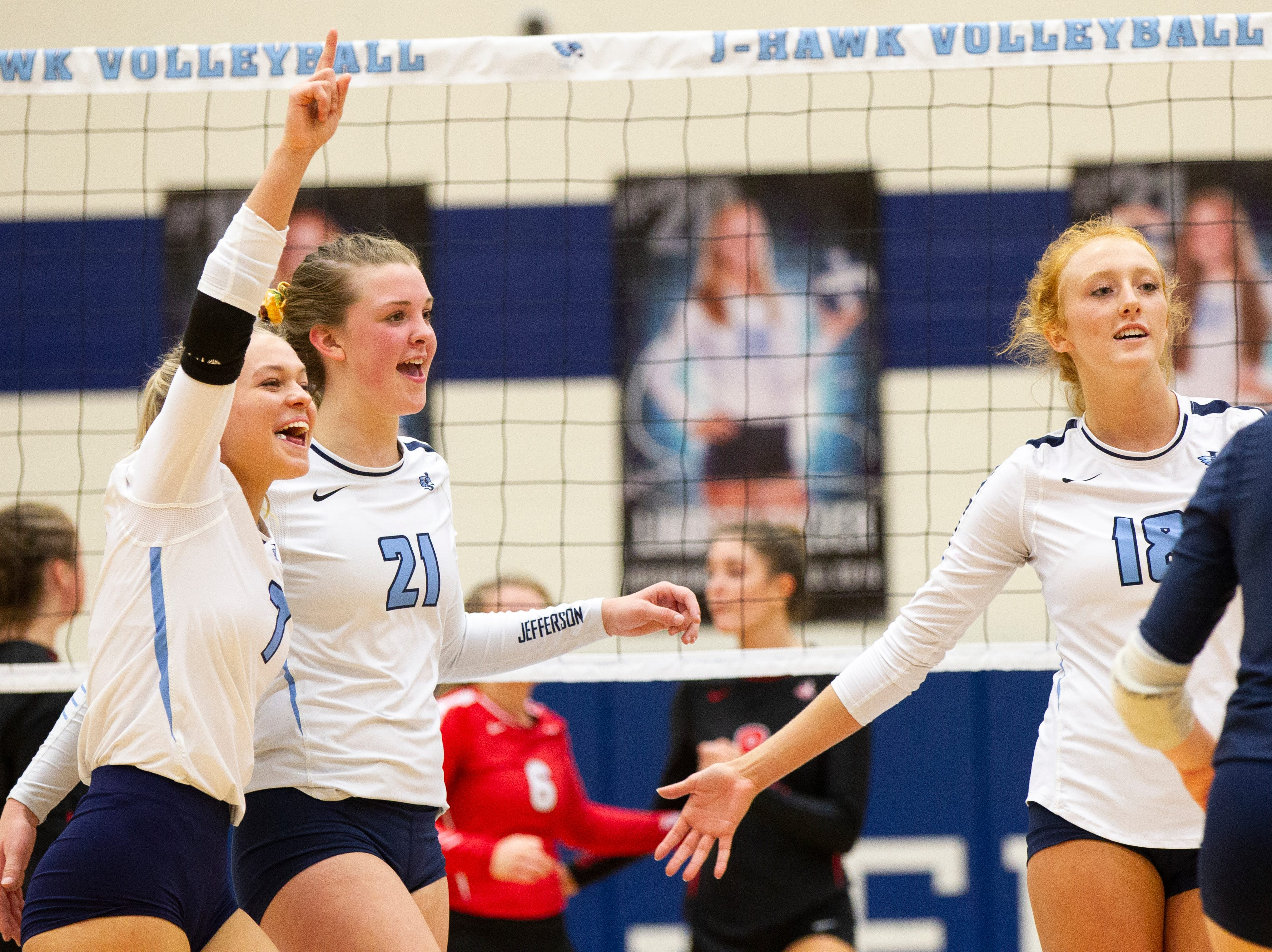 Cedar Rapids Jefferson's Allie Krousie (7) Sydney Kloubec (21) and Maggie Peters (18) celebrate a point during a Class 5A volleyball regional final game on Monday, Oct. 29, 2018, at Jefferson High School in Cedar Rapids.