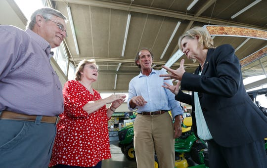In this Friday, Sept. 7, 2018 photo, appointed Republican U.S. Sen. Cindy Hyde-Smith of Mississippi, right, campaigns in Greenwood, Miss., with soybean farmers, Larry and Candy Davis. left, and rice farmer Mike Wagner. Hyde-Smith is running in a special election in November to fill the unexpired term of U.S. Sen. Thad Cochran, R-Miss., who retired in April. She faces fellow Republican, state Sen. Chris McDaniel, who almost unseated Cochran four years ago, Mike Espy, a Democrat and President Bill Clinton's first agriculture secretary, and Tobey Bernard Bartee, a former military intelligence officer who is also a Democrat. Party labels do not appear on the ballot. (AP Photo/Rogelio V. Solis)