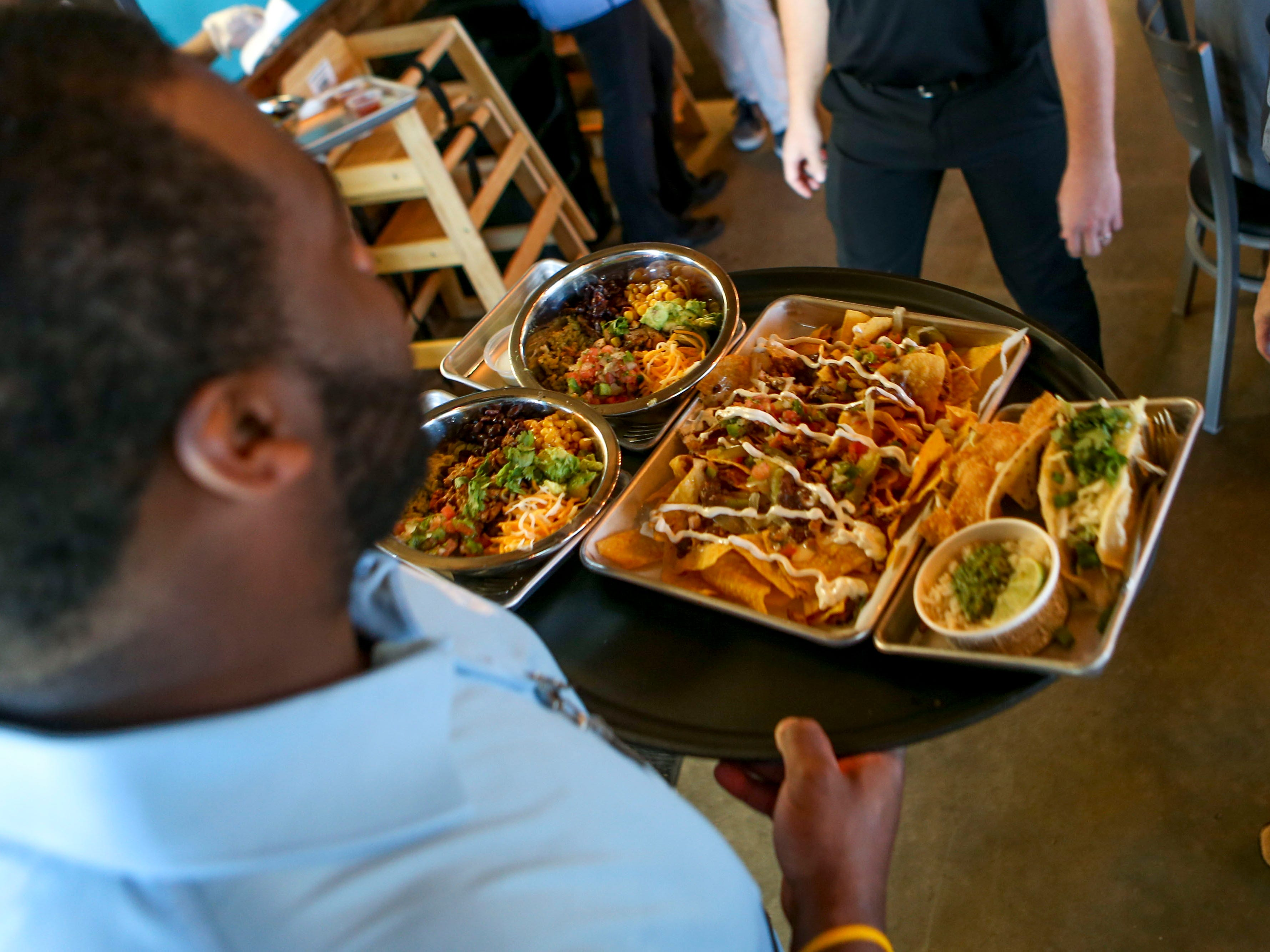 An employee presents a meal to a patron during the soft opening at Tacos 4 Life, a new restaurant in Jackson, Tenn., on Monday, Oct. 29, 2018.