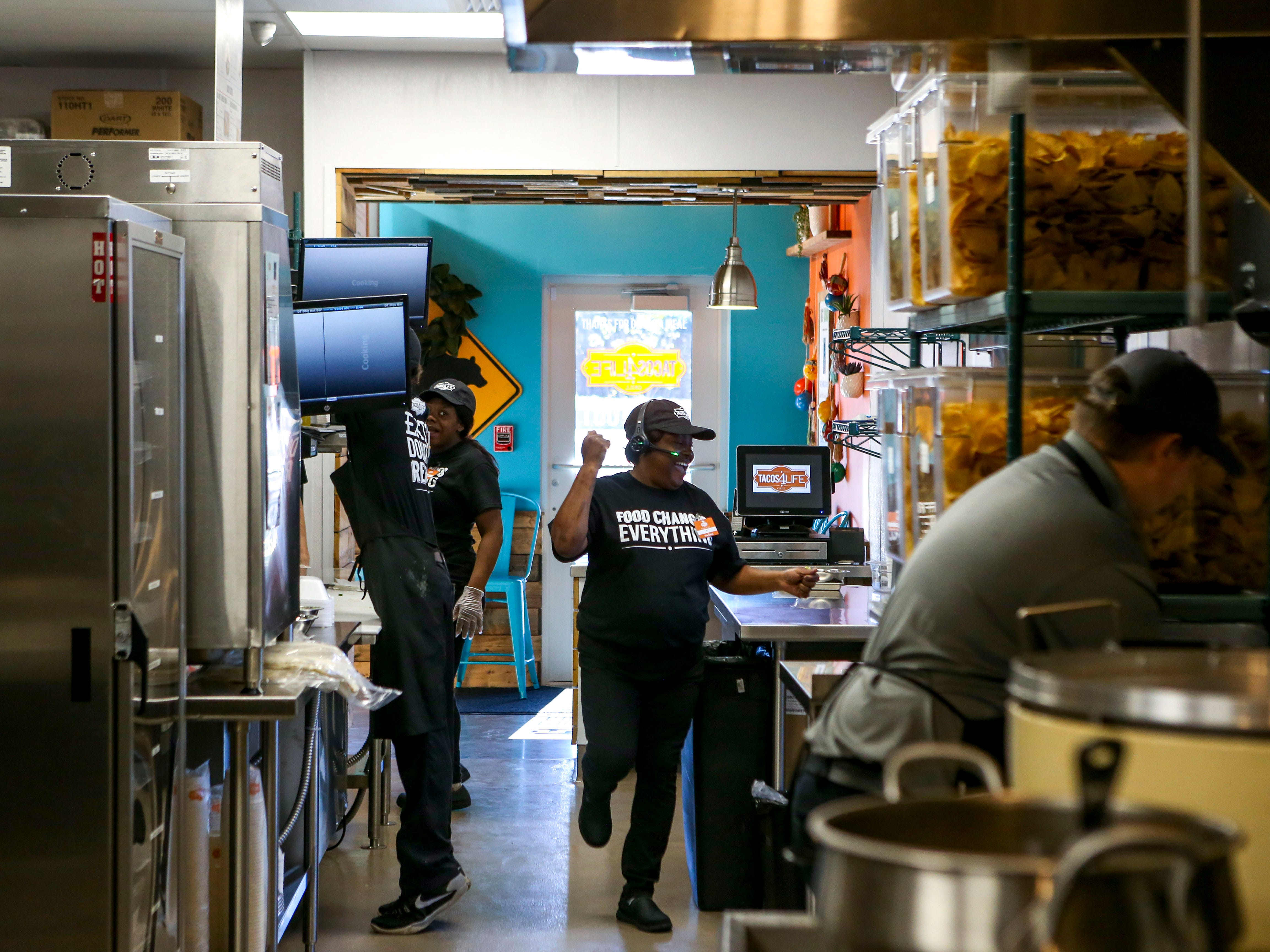 Employees take orders at the drive-thru during the soft opening at Tacos 4 Life, a new restaurant in Jackson, Tenn., on Monday, Oct. 29, 2018.