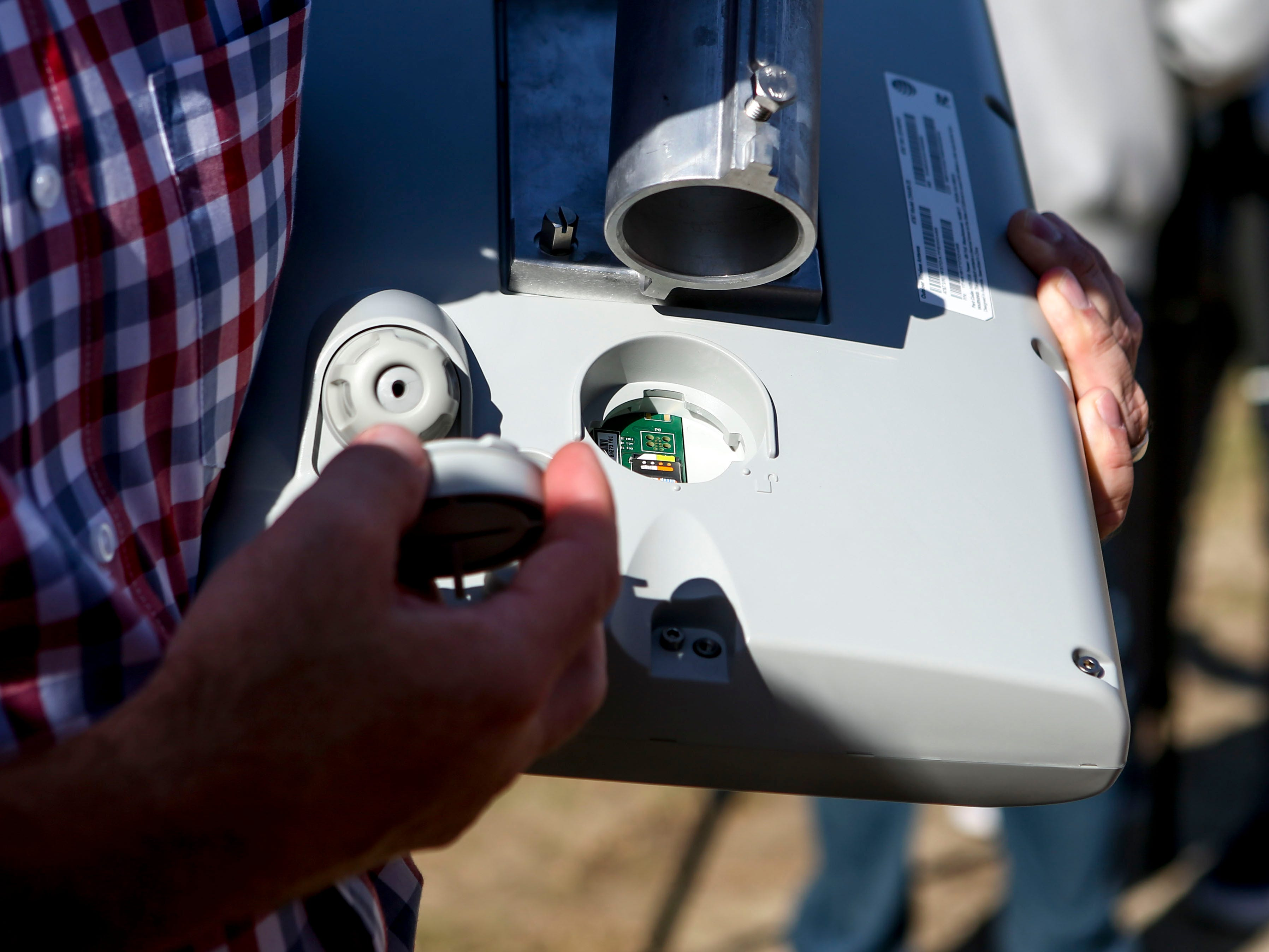 Ryan Porter, chief operating officer of Jackson Chamber, examines the SIM card slot of a receiver that will be used to spread wireless broadband internet during a ceremonial opening for the expansion of wireless broadband coverage through AT&T cell towers at 4567 Brownsville Hwy in Denmark, Tenn., on Tuesday, Oct. 30, 2018.