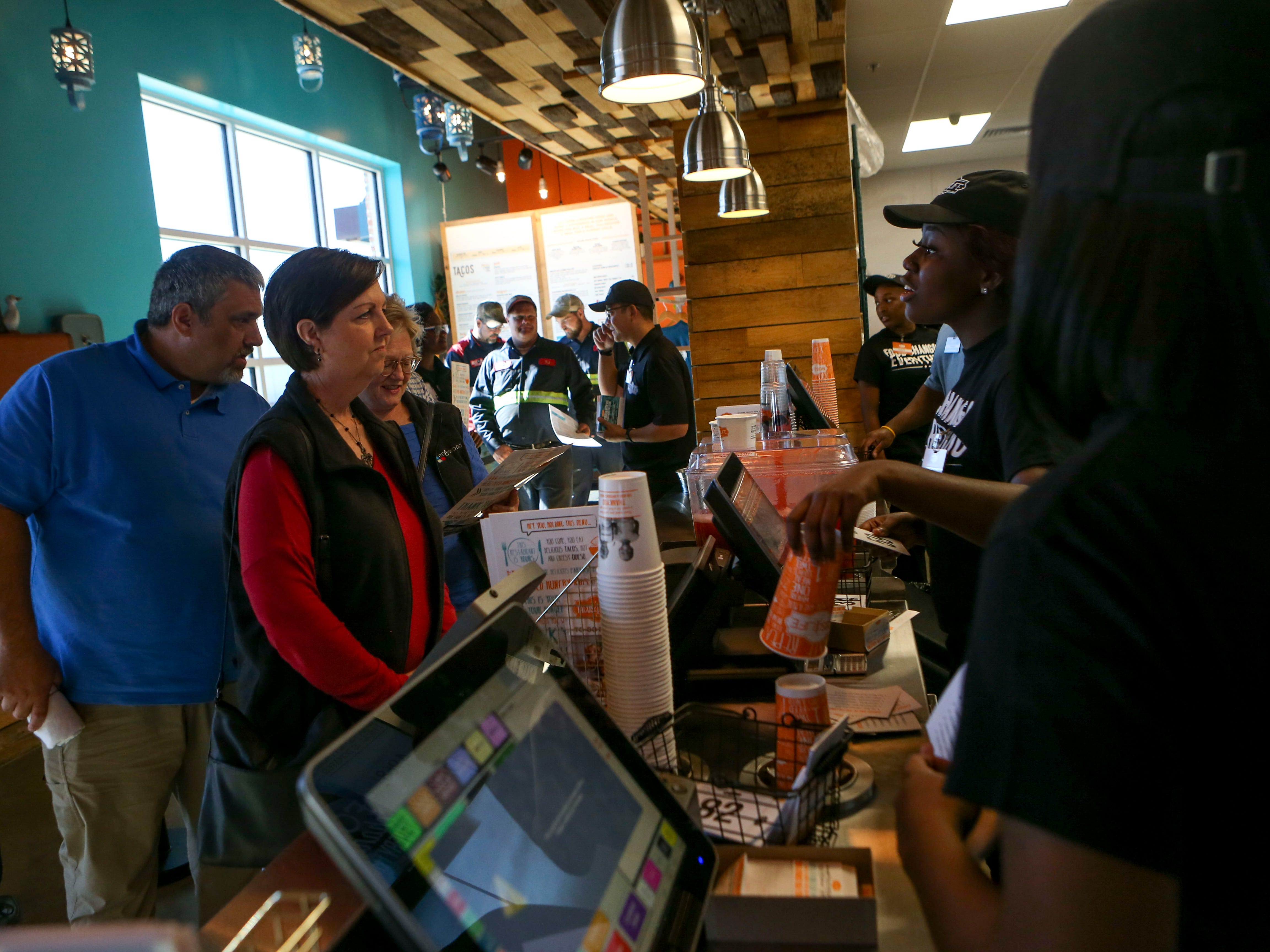 Cashiers take orders from patrons during the soft opening at Tacos 4 Life, a new restaurant in Jackson, Tenn., on Monday, Oct. 29, 2018.