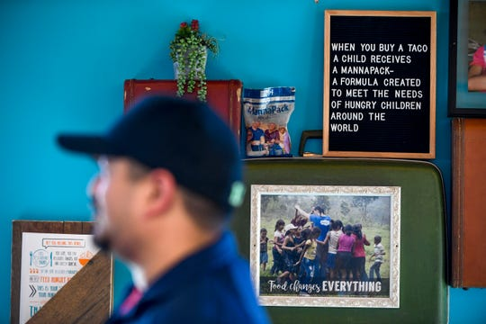 """A sign with accompanying photos describe the """"MannaPack"""" meals provided to hungry children is displayed on the front wall next to the registers during the soft opening at Tacos 4 Life, a new restaurant in Jackson, Tenn., on Monday, Oct. 29, 2018."""