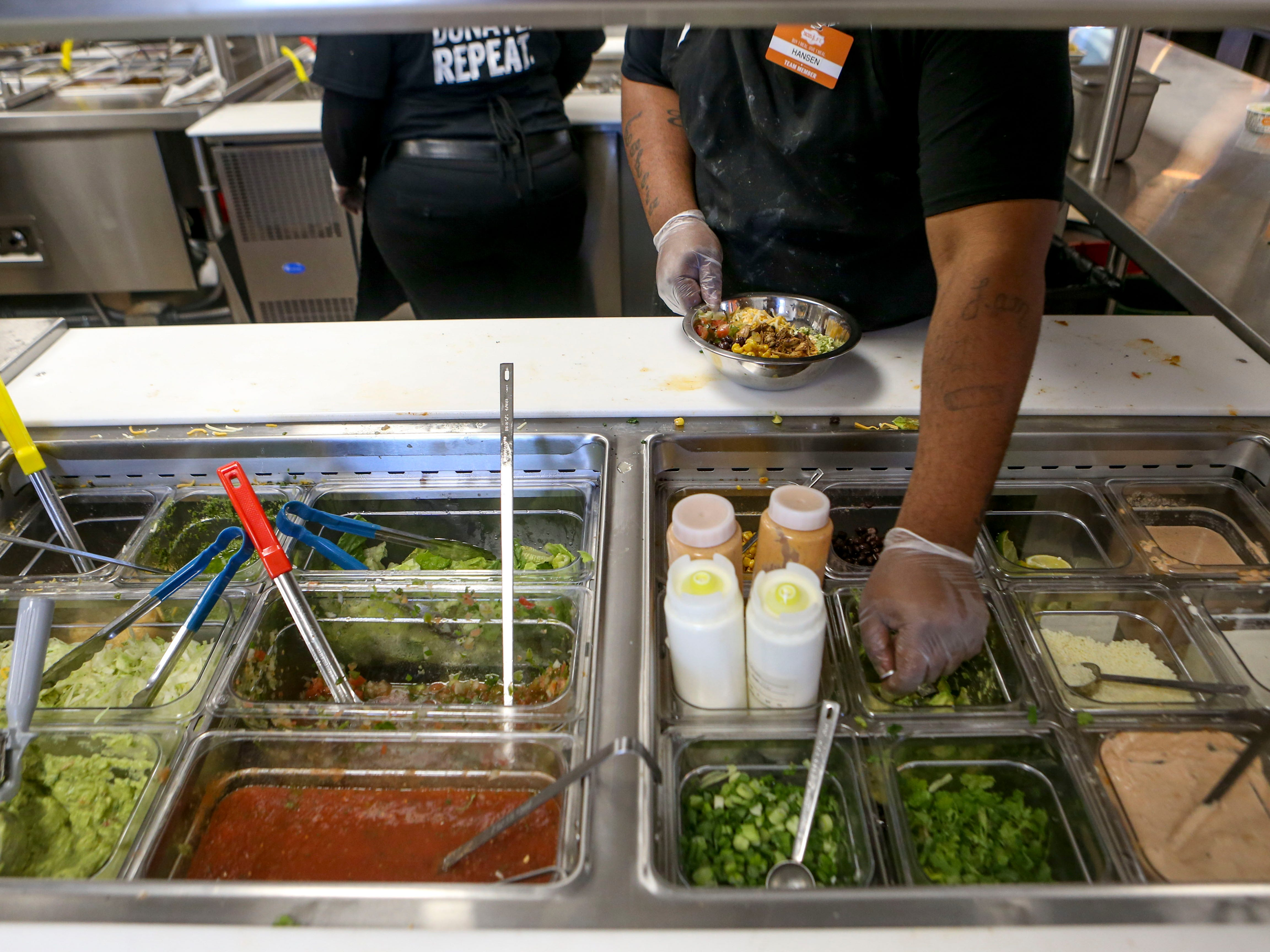 Employees reach out for ingredients to top on tacos during the soft opening at Tacos 4 Life, a new restaurant in Jackson, Tenn., on Monday, Oct. 29, 2018.