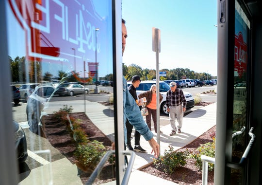 Patrons pull open the front door during the soft opening at Tacos 4 Life, a new restaurant in Jackson, Tenn., on Monday, Oct. 29, 2018.