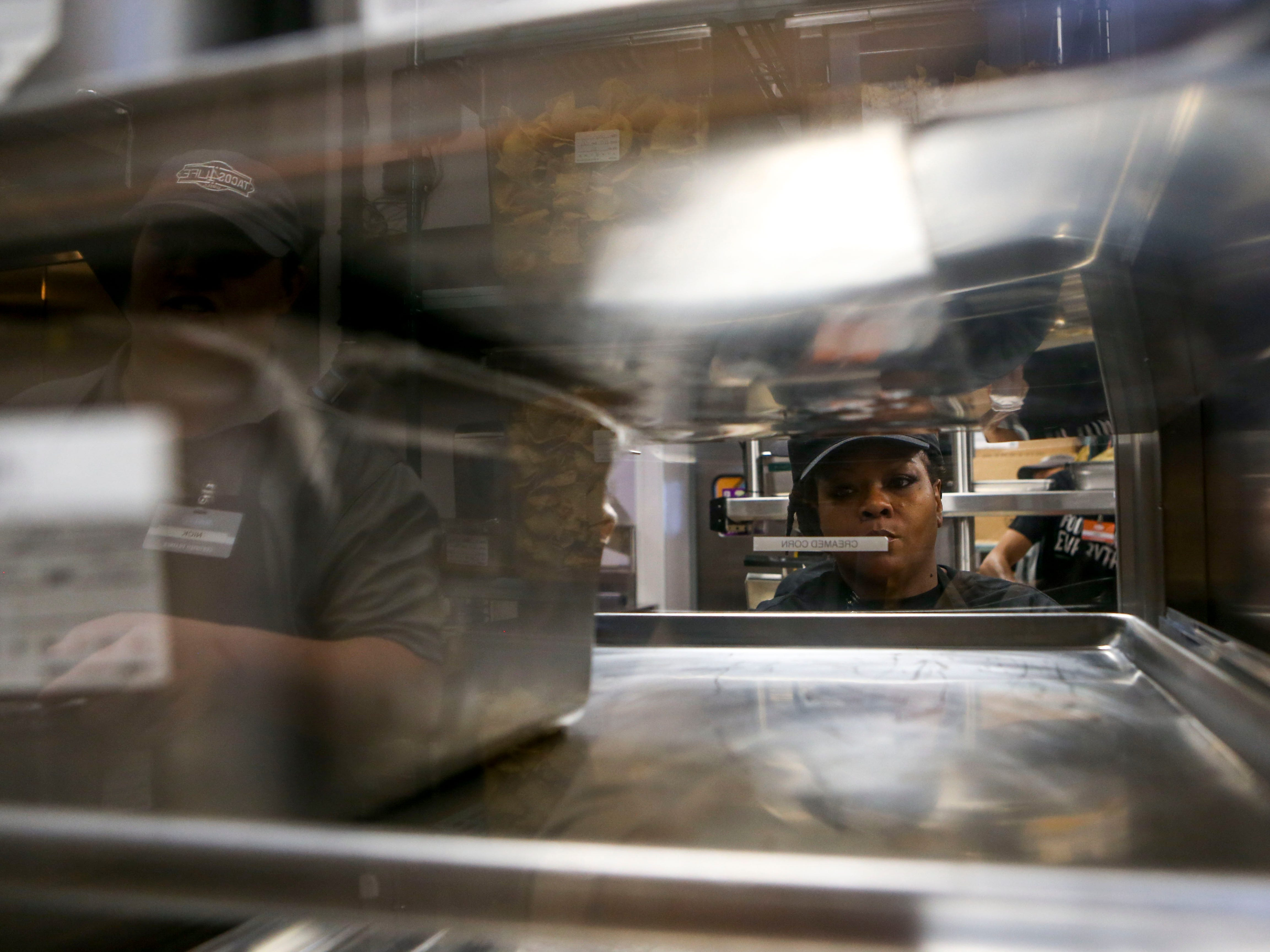 Employees grab trays with ingredients for tacos during the soft opening at Tacos 4 Life, a new restaurant in Jackson, Tenn., on Monday, Oct. 29, 2018.