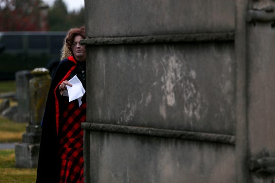 A speaker waits behind a mausoleum for her turn to present a monologue during Ghost Walk tour at Riverside Cemetery in Jackson, Tenn., on Friday, Oct. 26, 2018.