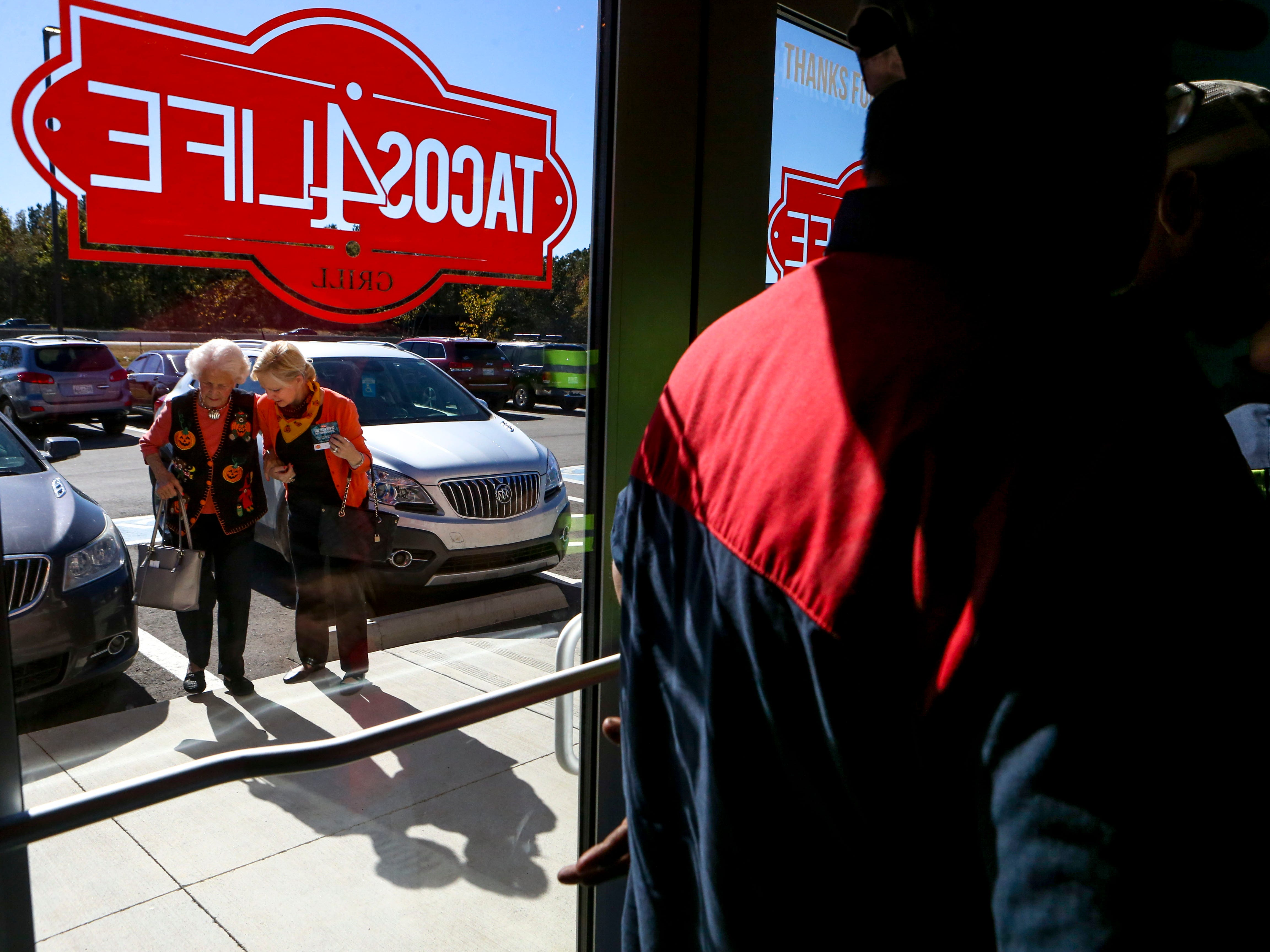 Patrons approach the entrance filled with people waiting in line during the soft opening at Tacos 4 Life, a new restaurant in Jackson, Tenn., on Monday, Oct. 29, 2018.