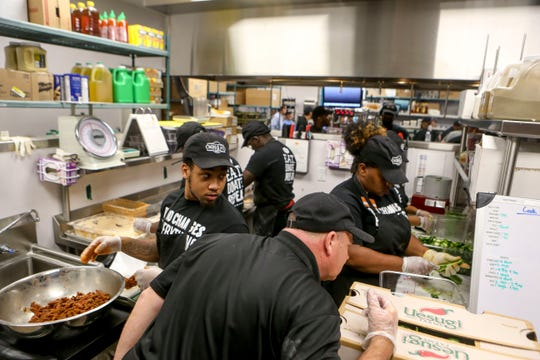 Employees prepare food in the back of the restaurant during the soft opening at Tacos 4 Life, a new restaurant in Jackson, Tenn., on Monday, Oct. 29, 2018.