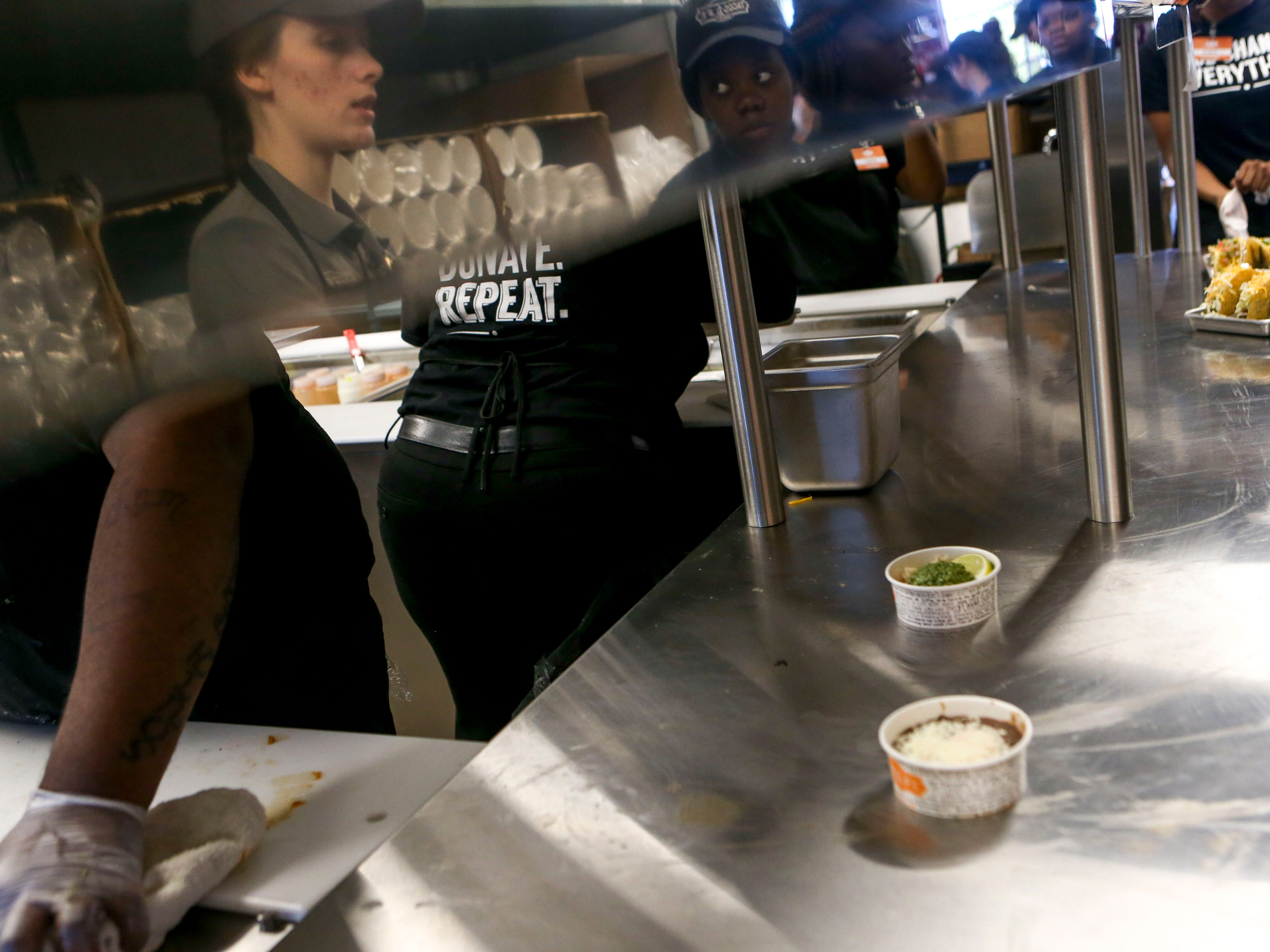 Employees wait for orders to arrive in the window during the soft opening at Tacos 4 Life, a new restaurant in Jackson, Tenn., on Monday, Oct. 29, 2018.