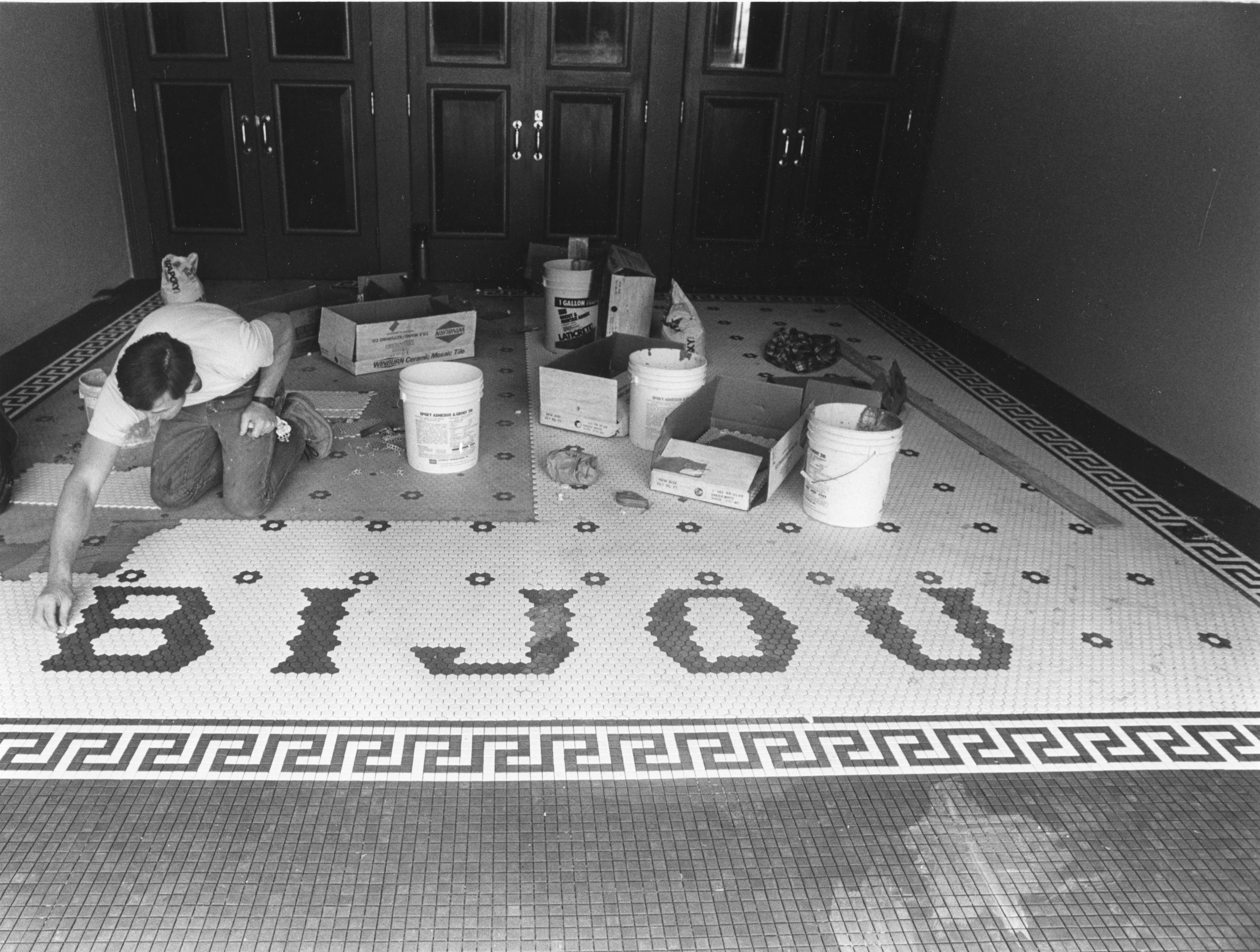 Ronnie Jenkins finds the hardest part of his job is being on your knees for so long. Jenkins, with John Beretta Tile Co., and another employee have been working on the foyer of the Bijou Theatre on October 25, 1985.
