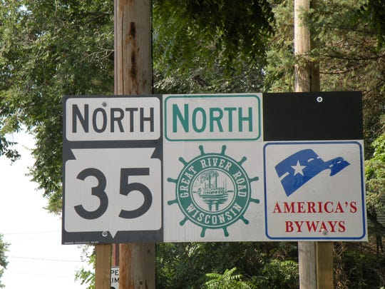 Motorists traveling along the Great River Road follow signs bearing the green pilot's wheel logo, shown here on Wisconsin's Highway 35. The National Scenic Byway along the Mississippi River offers natural, cultural, historical, recreational and scenic properties.
