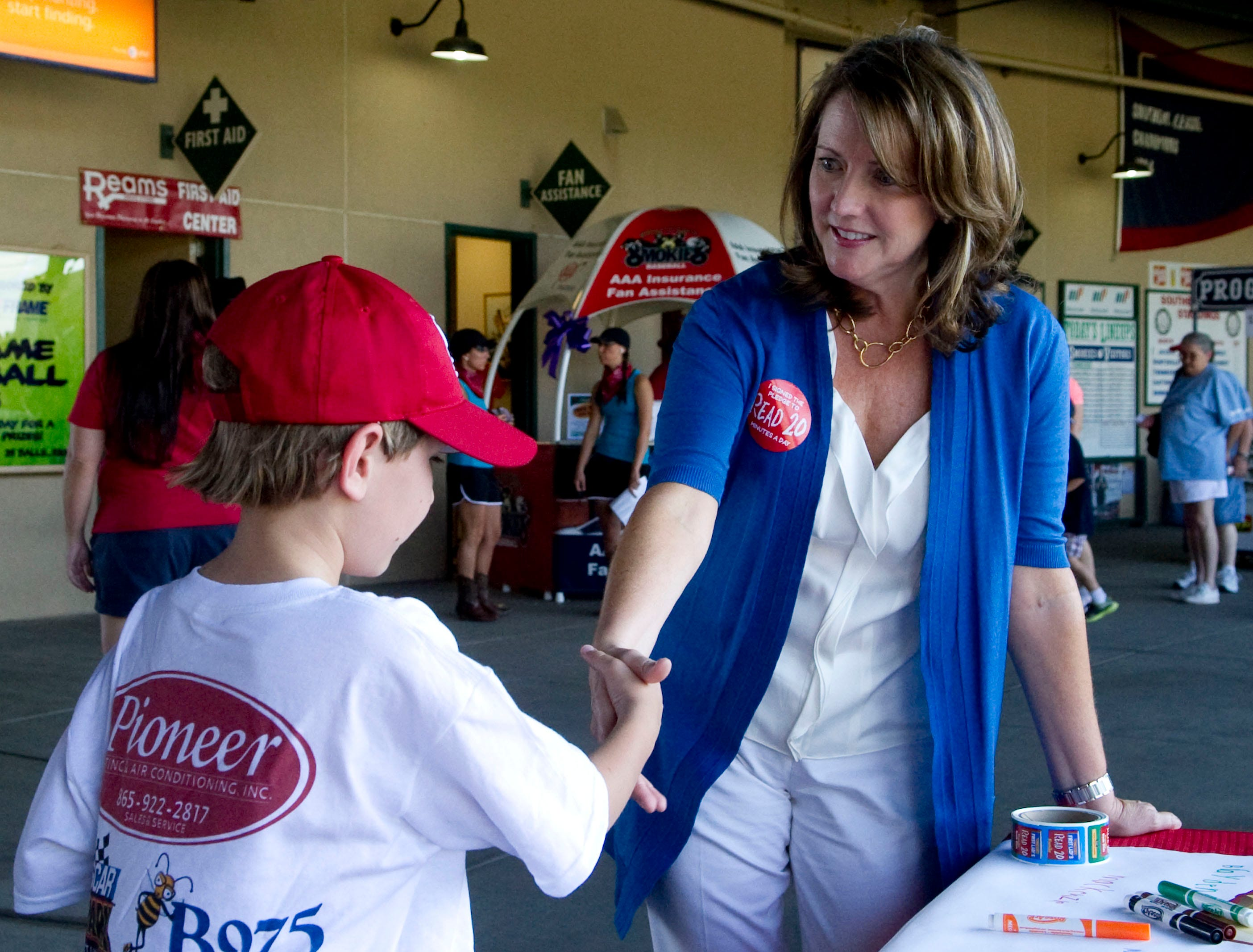 """Tennessee First Lady Crissy Haslam shakes hands with  Joel Mobley, 8, during a Tennessee Smokies game on Wednesday, June 13, 2012. Mobley received a book, """"Frindle"""" by Andrew Clements, from the First Lady who was at the park to promote her Read20 Book Club, an initiative her office to promote reading with children for at least 20 minutes a day."""