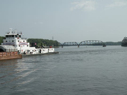 A towboat and barge pass the paddlewheeler, La Crosse Queen, as it navigates through one of the Mississippi River's oldest railroad swing bridges, located near La Crosse, Wis.
