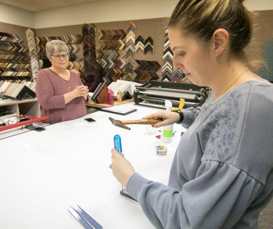 Mara Ikens, right, assembles a small frame Tuesday, Oct. 30, 2018 in the new location for ArtVentures. She and her husband bought the business from Claudia Roblee, in the background, and her husband Mark Gougherty.