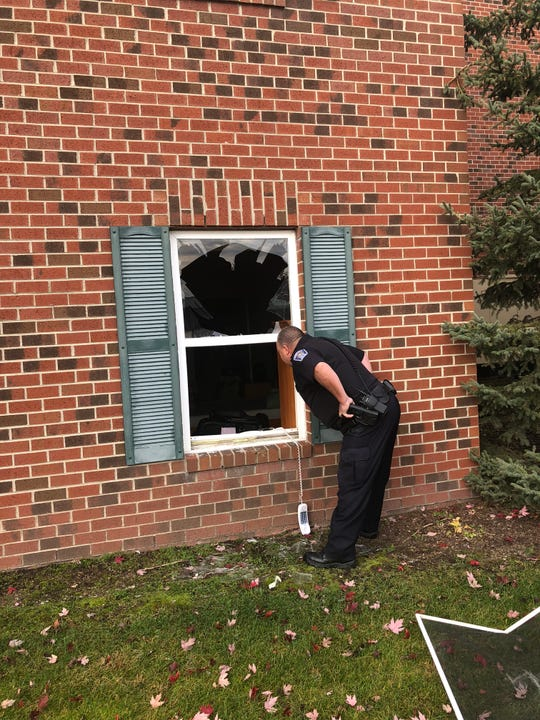 A Brighton Police officer checks out the damage a deer left after it smashed into a bedroom at Independence Village Retirement Community on Oct. 30, 2018.
