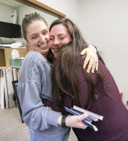 With tears on her cheeks, Katie Gougherty, right, hugs ArtVentures new co-owner Mara Ikens Tuesday, Oct. 30, 2018. The framing business has moved from the location where Gougherty's family operated the business for years, and the transition proved to be an emotional one for the former owners' daughter.
