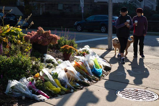 Pedestrians make their way past a collection of flowers placed for victims of the synagogue shooting along Shady Avenue in Pittsburgh, Pennsylvania on Tuesday morning. Oct. 30, 2018