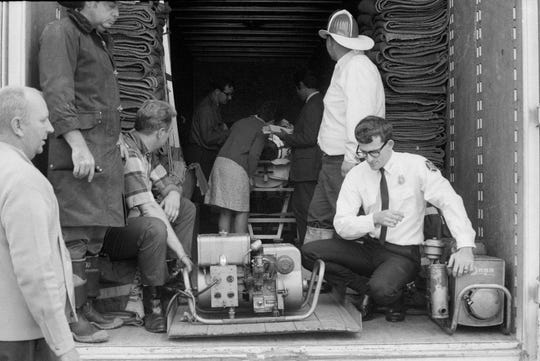 Firefighters watch over a generator used to power Bill Ashley's iron lung before taking him to vote in the 1968 election. Ashley and his wife Dorthea can be seen in the background.  By Charles Fentress Jr., The Courier-Journal. Nov. 5, 1968