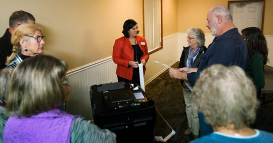 Lindsey LaForte, Recording Secretary with the Ingham County Clerk's office, middle, teaches election workers how to use an ICP, or voting tabulator, Wednesday, October 24, 2018, during election inspector training in Mason.