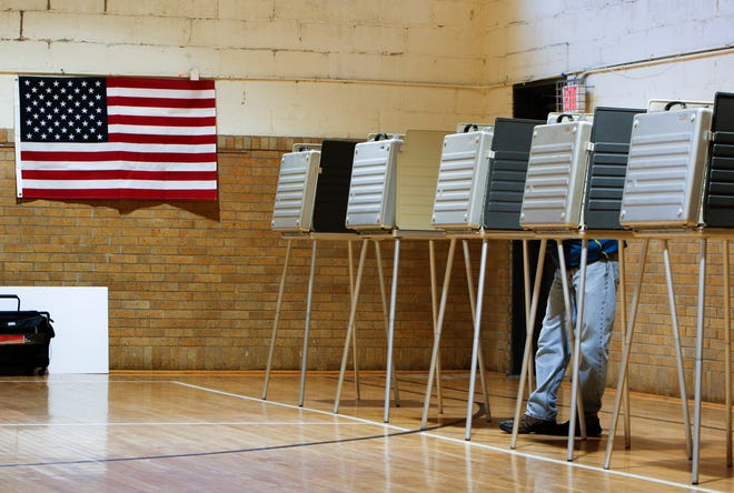 A lone voter casts his ballot Tuesday afternoon, Nov. 7, 2017, at Foster Community Center in Lansing.