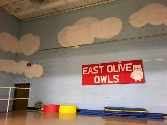 "A sign that reads ""East Olive Owls,"" hangs on the stage in the former East Olive Elementary School on Monday, Oct. 29, 2018. The building will reopen as East Olive Community Center on Nov. 3."