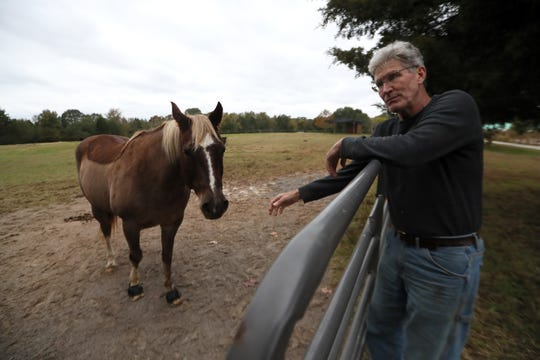 Rick Sievers leans on the gate of his horse pen at Sycamore Hill Farms in Collierville, where he has lived for 14 years. Sievers, who has an 80-acre plot of land, is afraid the proposed development of Quinn Ridge, near his property, will bring a dense living landscape that conflicts with the current, sprawling rural area he calls home.